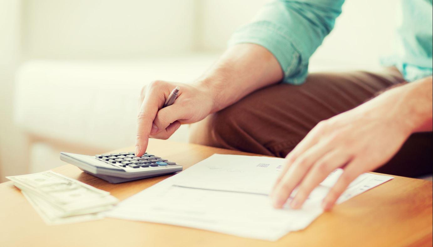 Man Using Calculator Franchise Cost